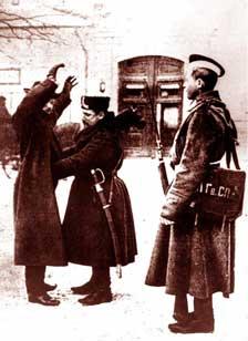 Полицейский офицер и солдат Семновского Гвардейского полка обыскивают прохожего на улице